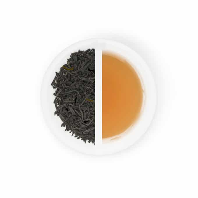 displays dried black Lapsang souchong leaves with the deep golden tea it produces